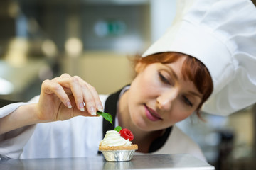 Focused head chef putting mint leaf on little cake