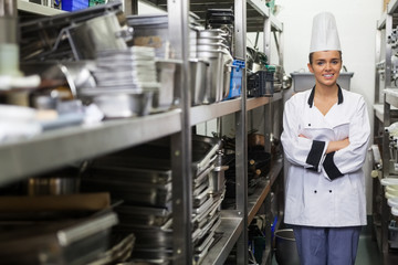 Young happy chef standing arms crossed between shelves