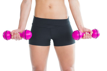 Close up of slender woman training with pink dumbbells