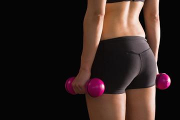 Rear view of slim woman wearing sportswear holding pink dumbbell