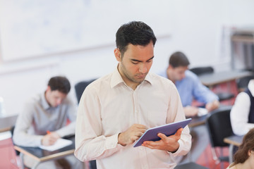 Male teacher working concentrated with his tablet