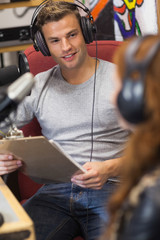 Attractive happy radio host interviewing a guest holding clipboa