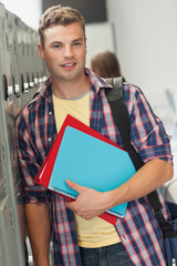 Happy handsome student standing next to locker
