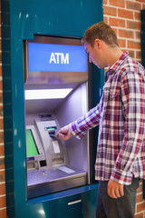 Handsome student withdrawing cash