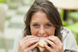 Close-up portrait of a female student eating sandwich