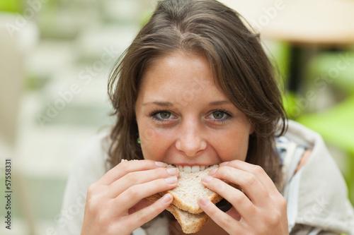 Zakończenie portret żeńskiego ucznia łasowania kanapka