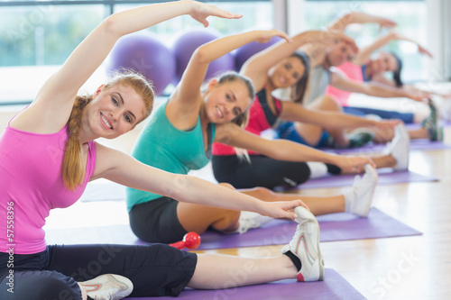 Fitness class and instructor doing stretching exercise on yoga m