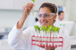 Female scientist analyzing young plants at lab