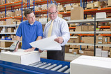Supervisor and worker examining paperwork and scanning boxes on production line in distribution warehouse