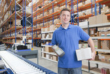 Portrait of smiling worker holding scanner and box at production line in distribution warehouse