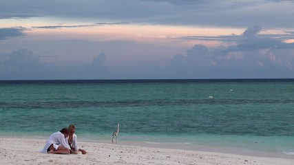 Two girls at the beach watching for the gray heron. Maldives.