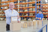Portrait of smiling supervisor leaning on box on production line in distribution warehouse