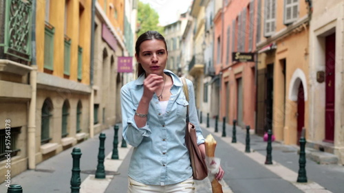 Woman walking on street and eating long baguette