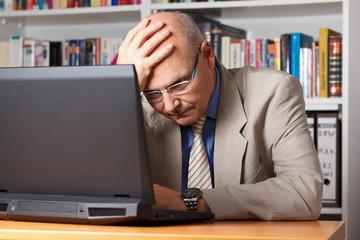 Genervter Senior vor seinem Laptop