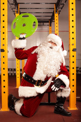 Santa Claus lifting weights in gym