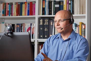 Mann mit Laptop, Headset und Kamera