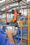 Worker operating robotic machinery in factory