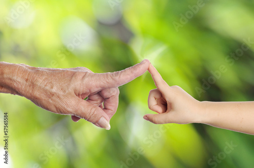 Senior's hand touching a child's hand on green nature background
