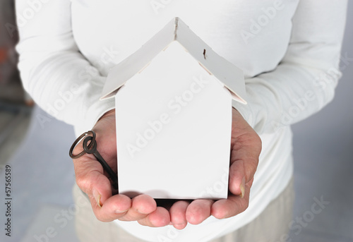 Old woman hands holding house model and key