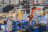 Worker controlling robotic machinery lifting steel fencing on production line in manufacturing plant