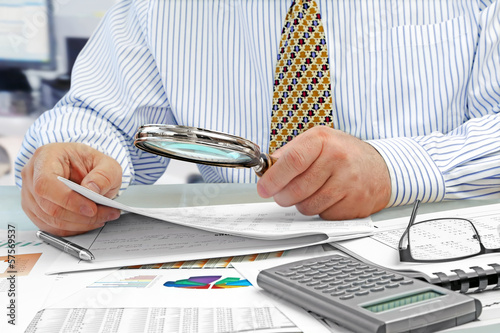 Male Hands with Magnifying Glass  Analyzing  Financial Data