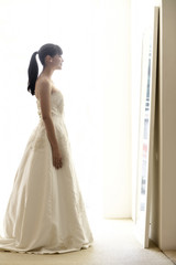 Young woman trying wedding dress on