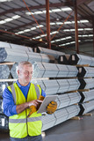 Worker with digital tablet in front of steel tubing in warehouse