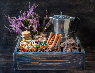 Сoffee beans, chocolate, spices and honey in a wooden box.