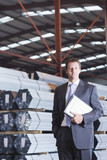 Portrait of confident businessman with paperwork in front of steel tubing in warehouse