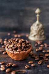 Vintage clay bowl with coffee beans on a wooden board
