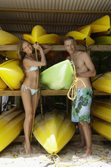 Mid adult couple taking out canoes
