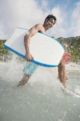 Young man with bodyboard walking in water