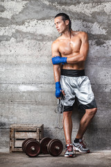 attractive boxer man standing on the wall and looking aside