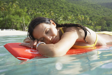 Young woman floating on bodyboard near beach
