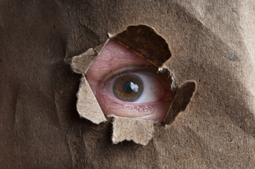 Human eye looking through hole cardboard