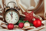Alarm clock with Christmas decoration on golden cloth