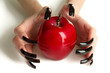 Hands with scary manicure holding red apple , isolated on white