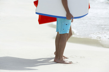 Two people with bodyboards standing on beach (low section)