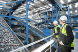 Businessmen watching plastic on conveyor belt in recycling plant