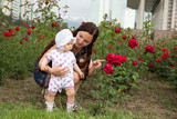 Happy mom and child girl hugging in flowers.