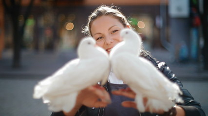 Beautiful, nice girl holding two white doves
