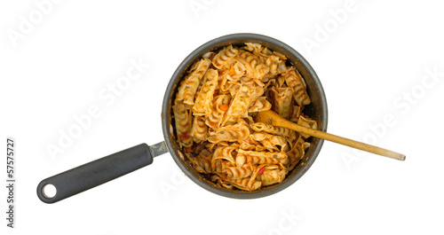 A small saucepan filled with cooked pasta and a spoon