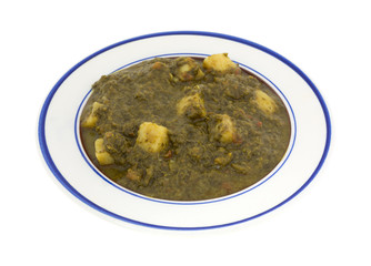 A serving of white potatoes in pureed spinach on a small plate