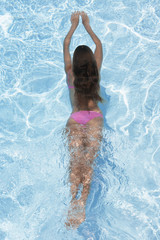 Mid adult woman diving in swimming pool (high angle view)