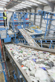 Businessman on platform above conveyor belts in recycling plant