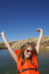 Young woman in life jacket stretching