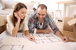 Cheerful couple looking at construction house plan
