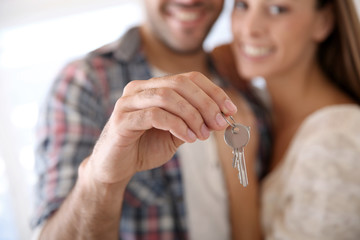 Closeup of house key held by young man