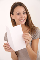 Cheerful girl on white background holding leaflet for message