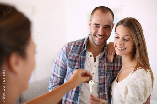 Cheerful couple getting keys of their new home